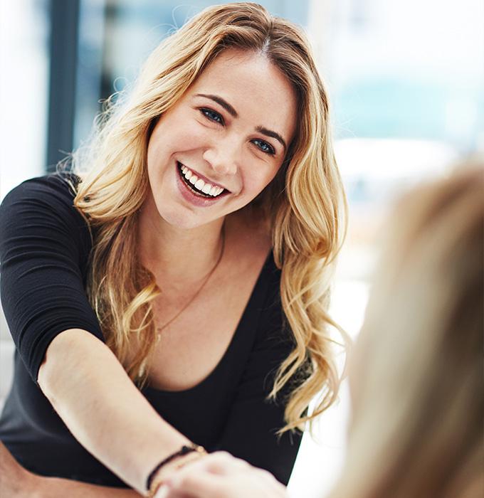Mujer estrechando la mano de otra mujer tras formalizar un contrato de formación y aprendizaje